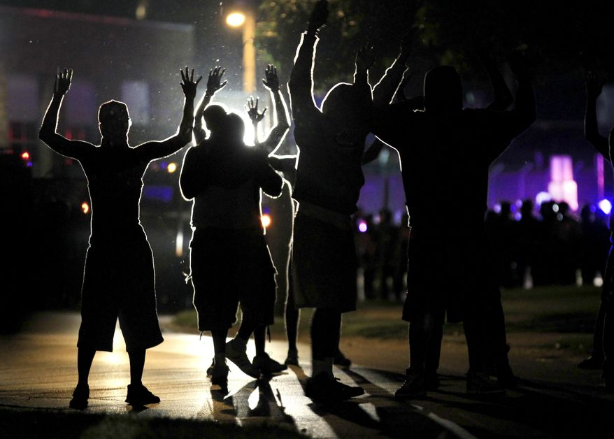 In this Aug. 11, 2014, file photo, people raise their hands in the middle of the street as police wearing riot gear move toward their position trying to get them to disperse, in Ferguson, Mo. (AP Photo/Jeff Roberson, File)
