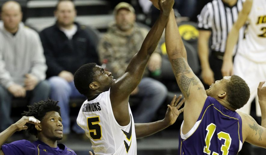 Iowa guard Anthony Clemmons, center, shoots between Alcorn State's Tamarcio Wilson, left, and Omar Beauperthuy, right, during the second half of an NCAA college basketball game, Tuesday, Dec. 9, 2014, in Iowa City, Iowa. (AP Photo/Charlie Neibergall)