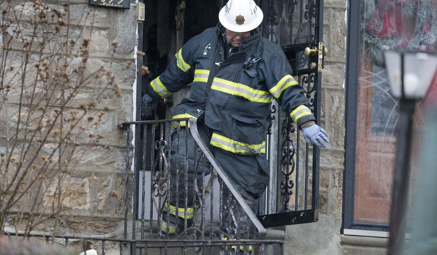 A fire marshal exits a burned out home in the aftermath of a fatal fire Tuesday, Dec. 9, 2014, in Philadelphia. A firefighter was trapped in the basement of the burning row home early Tuesday, becoming the first female member of the Philadelphia Fire Department to die in the line of duty, officials said. The 11-year veteran was part of the first company deployed to a fire in the basement of the home in the city's West Oak Lane neighborhood at about 3 a.m. Tuesday, fire commissioner Derrick Sawyer said. (AP Photo/Matt Rourke)