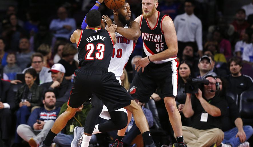 Detroit Pistons forward Greg Monroe (10) drives on Portland Trail Blazers guard Allen Crabbe (23) and Chris Kaman (35) in the first half of an NBA basketball game in Auburn Hills, Mich., Tuesday, Dec. 9, 2014. (AP Photo/Paul Sancya)