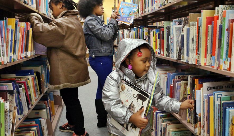 In this Wednesday , Nov. 26, 2014 photo, Sisters Yasmin Ousley, 10, left, Corionna King, 12 and Keiris Ousley, 3, look for books at the Ferguson Municipal Public Library in Ferguson, Mo. The Ferguson Municipal Public Library has received more than $350,000 in donations and gifts of books that will keep the library cataloger busy for some time. Contributions have soared since Nov. 24, when the library decided to stay open despite protests over a grand jury's decision to not indict officer Darren Wilson in the death of Michael Brown. (AP Photo/St. Louis Post-Dispatch, J.B. Forbes)  EDWARDSVILLE INTELLIGENCER OUT; THE ALTON TELEGRAPH OUT