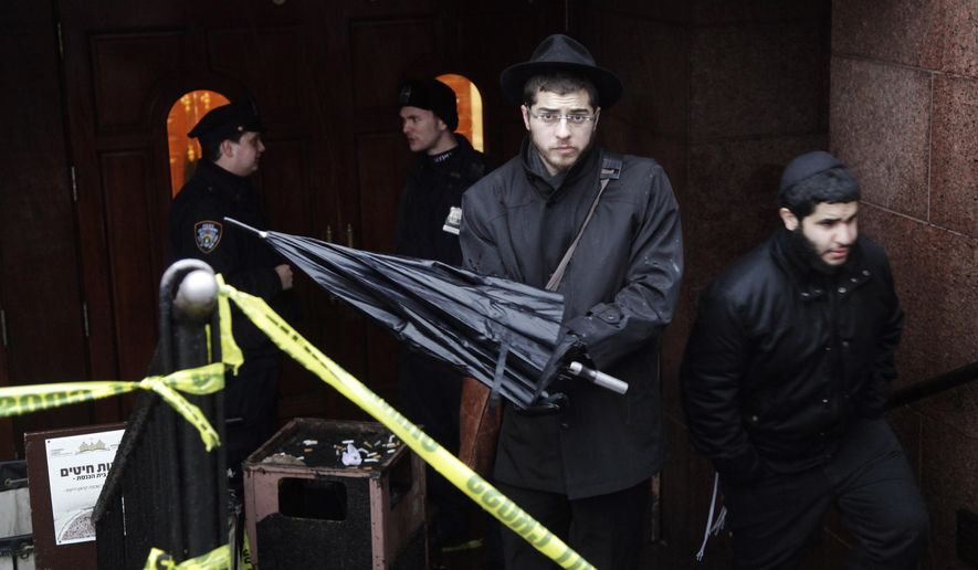 A member of the Lubavitch community, center, leaves the Chabad-Lubavitch Hasidic headquarters guarded by members of the New York Police Department, left, Tuesday, Dec. 9, 2014, in New York. A knife-wielding man stabbed an Israeli student inside the Brooklyn synagogue before being fatally shot by police after he refused to drop the knife. The student, Levi Rosenblatt, is in stable condition. (AP Photo/Mark Lennihan)