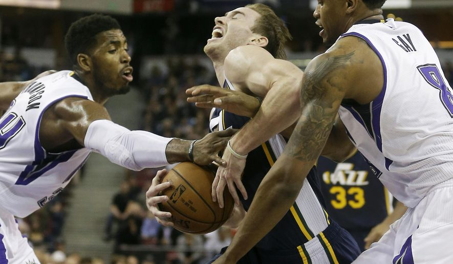 Utah Jazz forward Gordon Hayward, center, is fouled by Sacramento Kings forward Rudy Gay, right, during the first quarter of an NBA basketball game in Sacramento, Calif., Monday, Dec. 8, 2014. At left is Kings forward Jason Thompson. (AP Photo/Rich Pedroncelli)
