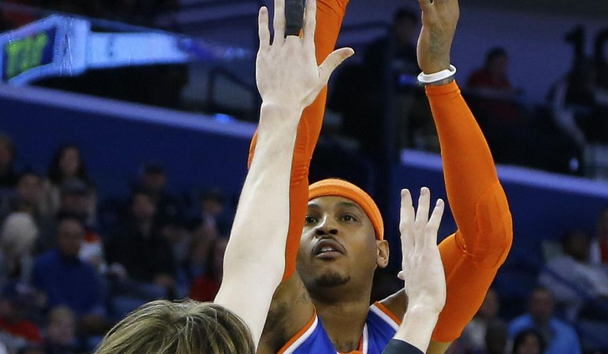 New York Knicks forward Carmelo Anthony, right, shoots over New Orleans Pelicans forward Luke Babbitt during the first half of an NBA basketball game in New Orleans, Tuesday, Dec. 9, 2014. (AP Photo/Jonathan Bachman)