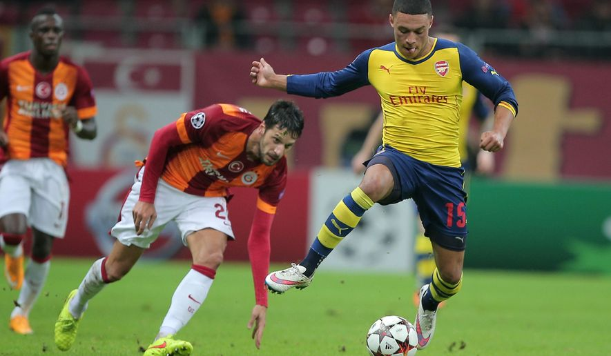 Arsenal's Alex Oxlade-Chaberlain, right, and  Hakan Balta of Galatasaray fight for the ball during their Champions League Group D soccer match at the Turk Telekom Arena Stadium in Istanbul, Turkey, Tuesday, Dec. 9, 2014. (AP Photo)