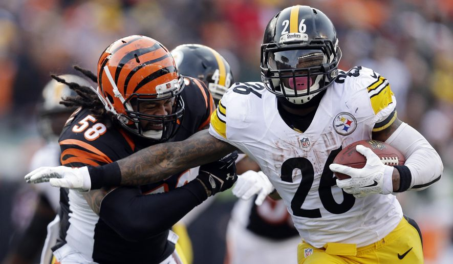 Pittsburgh Steelers running back Le'Veon Bell (26) gets past Cincinnati Bengals middle linebacker Rey Maualuga (58) on a 13-yard touchdown run during the second half of an NFL football game Sunday, Dec. 7, 2014 in Cincinnati. (AP Photo/Michael Conroy)