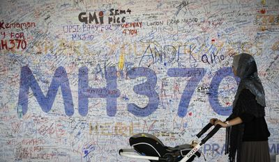In this March 19, 2014, file photo, a woman pushes her baby cart in front of the messages board for passengers aboard a missing Malaysia Airlines plane at Kuala Lumpur International Airport in Sepang, Malaysia. (AP Photo/Vincent Thian, File)