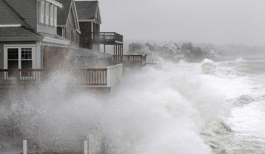 Waves splash against a seawall and onto houses along the Atlantic coast, Tuesday, Dec. 9, 2014, in Scituate, Mass. The National Weather Service posted a flood watch for urban and poor drainage areas, and a coastal flood advisory for the midday high tide cycle. (AP Photo/Steven Senne)