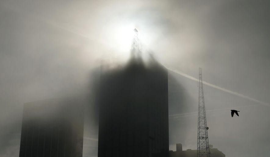 Downtown Dallas is enveloped  in morning fog, on Tuesday, Dec. 9, 2014. The National Weather Service issued a dense fog advisory Tuesday morning for the Dallas-Fort Worth area. The heavy fog has delayed some flights in North Texas.  (AP Photo/The Dallas Morning News, Evans Caglage)