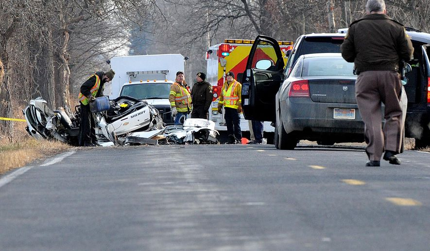 Ingham County Sheriff's deputies and emergency workers clear the scene of a fatal accident Sunday, Dec. 7, 2014 near Stockbridge Township, Mich. A deputy was killed after crashing his patrol vehicle while pursuing a fleeing driver.  (AP Photo/Lansing State Journal, Robert Killips)