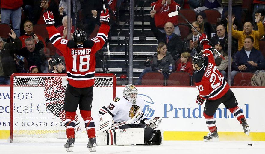 New Jersey Devils right wing Jordin Tootoo (20), right wing Steve Bernier (18) and right wing Stephen Gionta (11) celebrate a goal by Tootoo on Chicago Blackhawks goalie Scott Darling (33) during the first period of an NHL hockey game, Tuesday, Dec. 9, 2014, in Newark, N.J. (AP Photo/Julio Cortez)