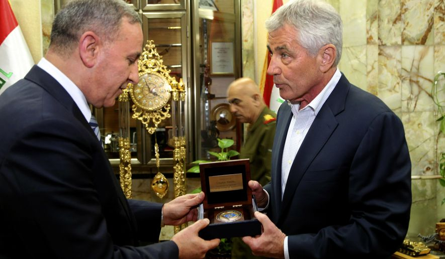 U.S. Secretary of Defense Chuck Hagel, right, offers a gift to his Iraqi counterpart Khalid al-Obeidi, in Baghdad, Iraq, Tuesday, Dec. 9, 2014. Iraqi Prime Minister Haider al-Abadi told U.S. Defense Secretary Chuck Hagel on Tuesday that his army is taking the offensive against the Islamic State group but needs more air power and heavy weaponry to prevail. (AP Photo)