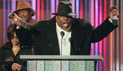 "Notorious B.I.G. 1972-1997 who won rap artist and rap single of the year, clutches his awards at the podium during the Billboard Music Awards in New York, in this Dec. 6, 1995 file photo.  On Friday, Nov. 16, 2007, a wrongful death lawsuit brought by the family of slain rapper Notorious B.I.G. against the city of Los Angeles may be amended to include several other defendants, including record executive Marion ""Suge"" Knight, a federal judge has ruled. The rapper, whose real name was Christopher Wallace, was shot and killed March 9, 1997, after a party at the Petersen Automotive Museum in Los Angeles.(AP Photo/Mark Lennihan, File)"