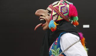 A dancer walks before a performance at the Climate Change Conference in Lima, Peru, Tuesday, Dec. 9, 2014. Delegates from more than 190 countries are meeting in Lima, to work on drafts for a global climate deal that is supposed to be adopted next year in Paris. (AP Photo/Juan Karita)