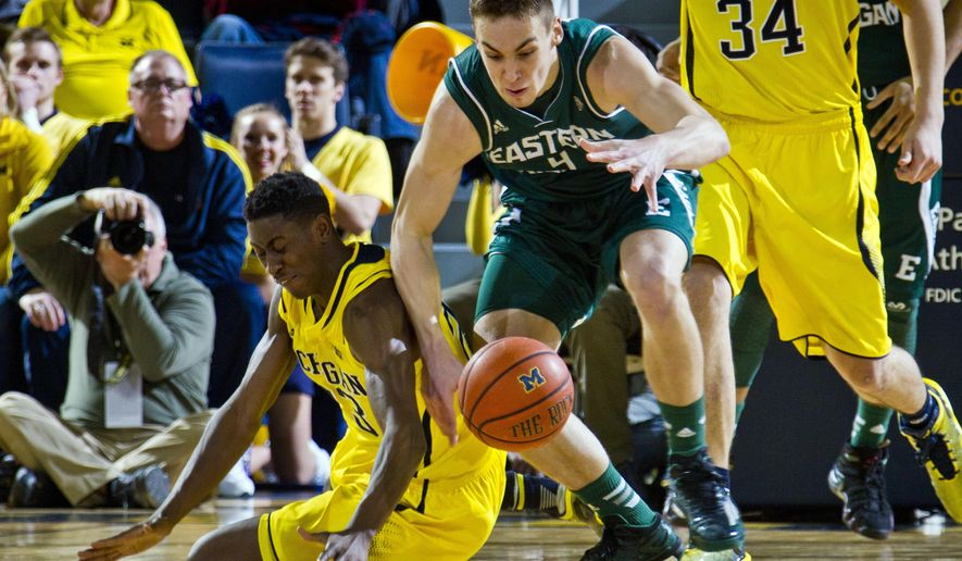 Michigan guard Caris LeVert, left, scrambles for a loose ball with Eastern Michigan forward Brandon Nazione (4) in the first half of an NCAA college basketball game at Crisler Center in Ann Arbor, Mich., Tuesday, Dec. 9, 2014. (AP Photo/Tony Ding)
