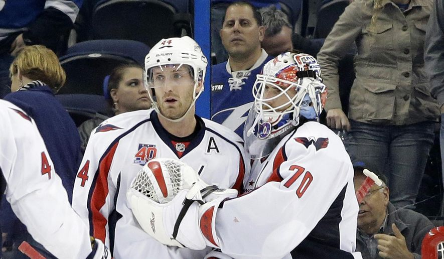 Washington Capitals goalie Braden Holtby (70) and defenseman Brooks Orpik (44) celebrate after the team defeated the Tampa Bay Lightning 5-3 during an NHL hockey game Tuesday, Dec. 9, 2014, in Tampa, Fla. (AP Photo/Chris O'Meara)