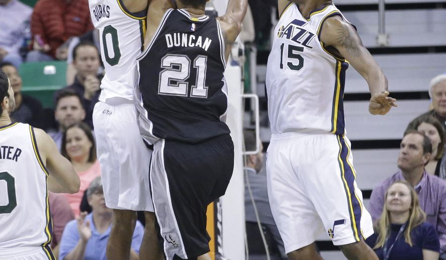 Utah Jazz's Derrick Favors (15) and Alec Burks (10) defend against San Antonio Spurs' Tim Duncan (21) in the fourth quarter during an NBA basketball game Tuesday, Dec. 9, 2014, in Salt Lake City. The Jazz won 100-96. (AP Photo/Rick Bowmer)