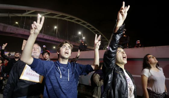 Protesters raise their hands as they chant Hands Up Don't Shoot under Highway 80 during a protest in response to police killings in Missouri and New York in Berkeley, Calif., Monday, Dec. 8, 2014. (AP Photo/Jeff Chiu) ** FILE **