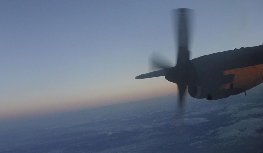 This photo taken Dec. 6, 2014, shows a propeller from the cockpit of a C130 military transport plane flying over the Alaska Range. The Alaska National Guard provided transport for the good Samaritan program Operation Santa, which took gifts and schools supplies to about 300 children in the Inupiat Eskimo community. (AP Photo/Mark Thiessen)