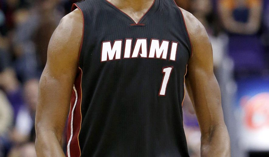 Miami Heat's Chris Bosh celebrates after hitting a 3-pointer against the Phoenix Suns during the second half of an NBA basketball game Tuesday, Dec. 9, 2014, in Phoenix.  The Heat won 103-97. (AP Photo/Ross D. Franklin)