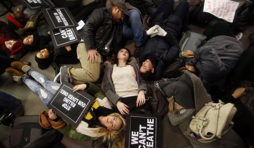 """FILE- In this Dec. 5, 2014 file photo, protesters rallying against a grand jury's decision not to indict the police officer involved in the death of Eric Garner stage a """"die-in"""" at the Apple Store on Fifth Avenue, in New York. Across the country, protesters angered at the killing of unarmed black men by white police officers have turned out in recent days in cities and towns. They are college students and grandmothers, experienced protesters as well as novices, often as many white as black. (AP Photo/Jason DeCrow, File)"""