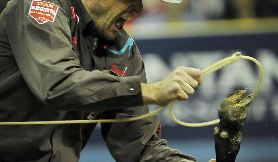 Clint Cooper of Decatur, Texas competes in the tie-down roping during the fifth go-round of the National Finals Rodeo at the Thomas & Mack Center on Monday, Dec. 8, 2014, in Las Vegas. (AP Photo/Las Vegas Review Journal, David Becker)
