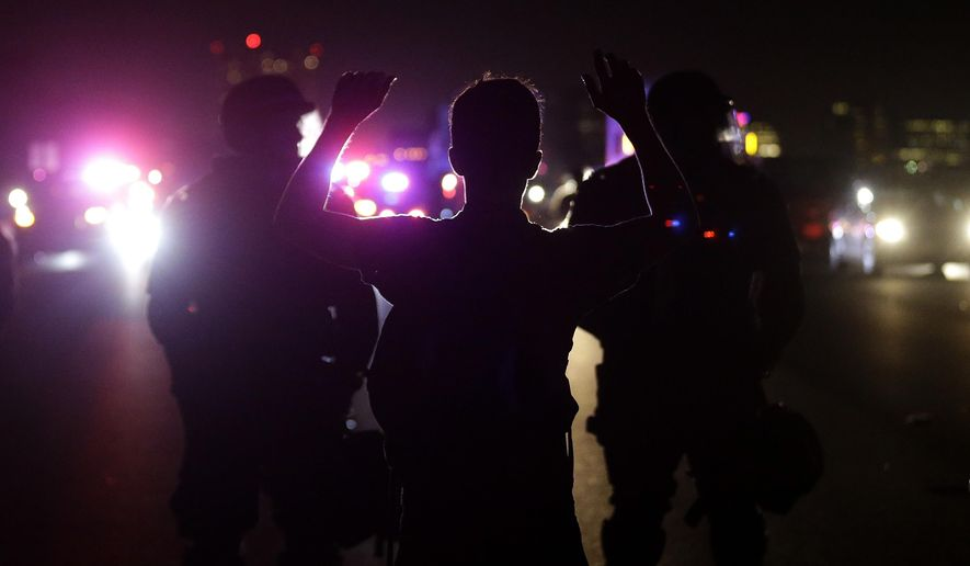 A protesters raises his arms as California Highway Patrol Officers stand in front of him as protesters block traffic on Highway 80 in Berkeley, Calif., Monday, Dec. 8, 2014. in response to police killings in Missouri and New York. (AP Photo/Jeff Chiu)