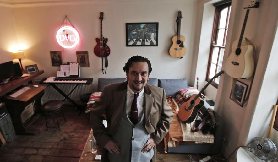 On this Friday, Dec. 5, 2014 photo, musician Tim Arnold, poses in his flat in central London's Soho district. The closure of Madame Jojo's, the venerable burlesque nightclub has ignited a battle between developers, locals and entertainers for the soul of Soho, the city's late-night hub, red-light district and creative heart. Arnold has enlisted friends and fellow performers to try and reverse the closure.  (AP Photo/Lefteris Pitarakis)