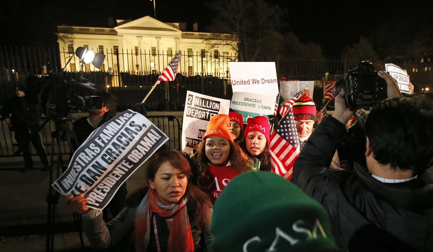 FILE - In this Nov. 20, 2014 file photo, people chant during a demonstration in front of the White House in Washington as President Barack Obama announced executive actions on immigration during a nationally televised address. The US judge assigned to rule in the lawsuit over President Barack Obama's changes to immigration rules last year accused the Obama administration of participating in criminal conspiracies to smuggle children into the country by reuniting them with parents living here illegally.  (AP Photo/Alex Brandon, File)