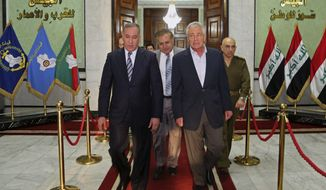 U.S. Secretary of Defense Chuck Hagel, second right, walks with his Iraqi counterpart Khalid al-Obeidi, left, in Baghdad, Iraq, Tuesday, Dec. 9, 2014. Iraqi Prime Minister Haider al-Abadi told U.S. Defense Secretary Chuck Hagel on Tuesday that his army is taking the offensive against the Islamic State group but needs more air power and heavy weaponry to prevail. (AP Photo)