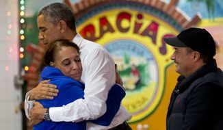 """In front of a sign that says """"Gracias,"""" meaning thank you in Spanish, President Barack Obama receives a hug from the owners of """"La Hacienda"""" restaurant, Lilia Yepez, left, and Carlos Yepez, before ordering food to go from the Mexican restaurant in Nashville, Tenn., Tuesday, Dec. 9, 2014. Earlier in the afternoon in Nashville the president spoke about his executive actions on immigration. (AP Photo/Jacquelyn Martin)"""