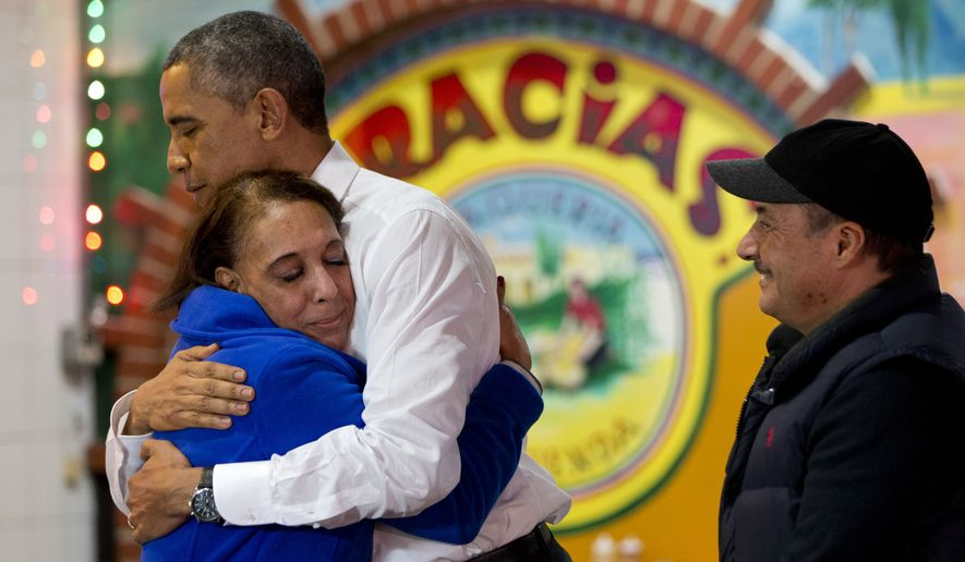 "In front of a sign that says ""Gracias,"" meaning thank you in Spanish, President Barack Obama receives a hug from the owners of ""La Hacienda"" restaurant, Lilia Yepez, left, and Carlos Yepez, before ordering food to go from the Mexican restaurant in Nashville, Tenn., Tuesday, Dec. 9, 2014. Earlier in the afternoon in Nashville the president spoke about his executive actions on immigration. (AP Photo/Jacquelyn Martin)"