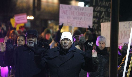 "In this photo taken on Monday night, Dec. 8, 2014, protestors chant ""hands up, don't shoot"" while walking down West Main Street toward the downtown Mall in Charlottesville, Va., during a march for justice in response to the national spotlight on police brutality. (AP Photo/The Daily Progress, Ryan M. Kelly)"