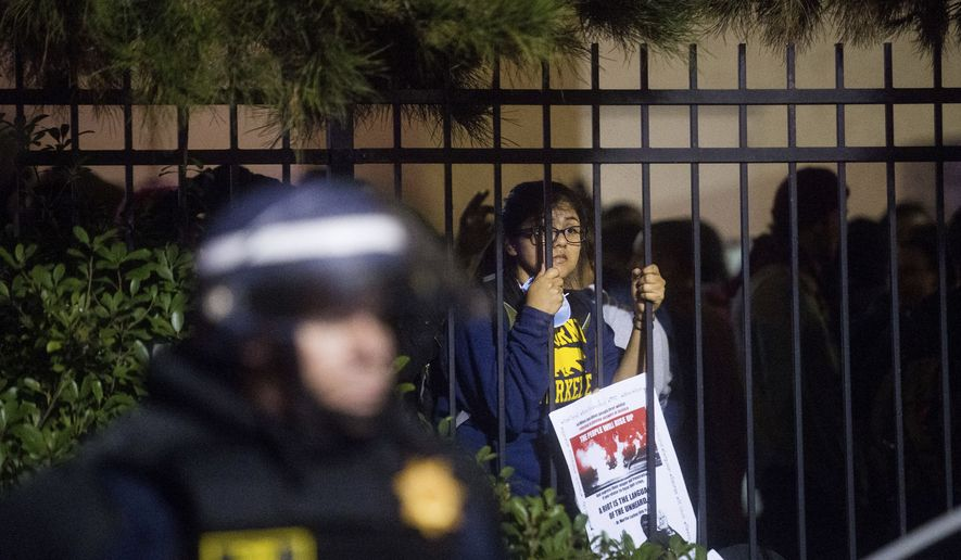 A protester, one of dozens detained by police after a group stormed Interstate 80, peers out from a behind a fence in Emeryville, Calif., on Monday, Dec. 8, 2014. Hundreds of people marched through Berkeley for a third night a row, blocking an interstate highway and stopping a train as activists rallied against grand jury decisions not to indict white police officers in the deaths of two unarmed black men. (AP Photo/Noah Berger)