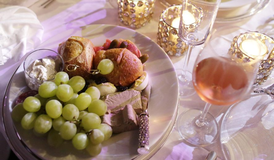 A plate of food is shown with candles and wine. (AP Photo/Lynne Sladky)