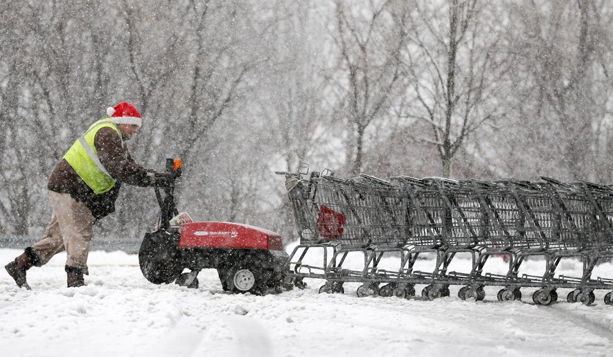 Nathan Osterhoudt pushes shopping carts through slushy snow at a Price Chopper supermarket on Wednesday, Dec. 10, 2014, in East Greenbush, N.Y. (AP Photo/Mike Groll)