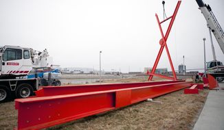 "In this Tuesday, Dec. 9, 2014 photo, a crew from the Davis Erection Company hoists up artist Mark di Suvero's installation, Big Mo, before the sculpture's unveiling ceremony at Tom Hanafan River's Edge Park in Council Bluffs, Iowa.  The nearly 76-feet high piece painted in ""spacetime orange"" has three legs and two moving parts on top that rotate in opposite directions. (AP Photo/The Daily Nonpareil, Joe Shearer)"