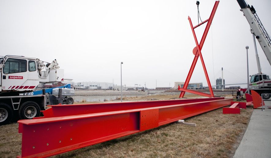 """In this Tuesday, Dec. 9, 2014 photo, a crew from the Davis Erection Company hoists up artist Mark di Suvero's installation, Big Mo, before the sculpture's unveiling ceremony at Tom Hanafan River's Edge Park in Council Bluffs, Iowa.  The nearly 76-feet high piece painted in """"spacetime orange"""" has three legs and two moving parts on top that rotate in opposite directions. (AP Photo/The Daily Nonpareil, Joe Shearer)"""