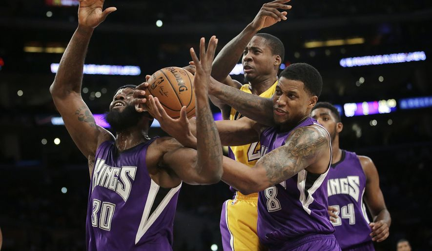 Sacramento Kings' Reggie Evans, left, and Rudy Gay, right, fight for a rebound with Los Angeles Lakers' Ed Davis during the first half of an NBA basketball game Tuesday, Dec. 9, 2014, in Los Angeles. (AP Photo/Jae C. Hong)