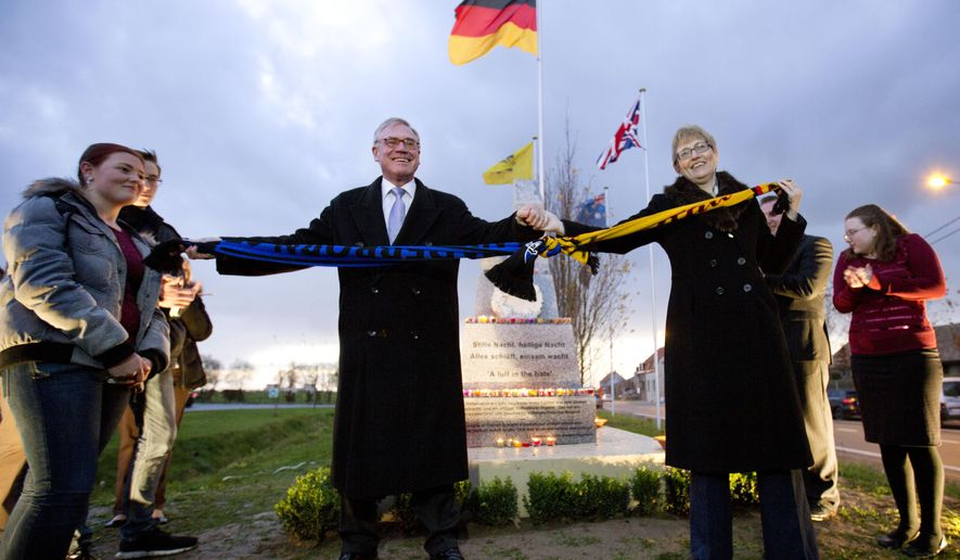 "British Ambassador to Belgium Alison Rose, center right, and German Ambassador to Belgium Eckart Cuntz, center left, hold two soccer scarves tied together during the inauguration of a Christmas Truce monument in Messines, Belgium on Saturday, Dec. 6, 2014. British students from the Mildenhall College Academy in Suffolk, UK and German students from the Gymnasium Theodorianum in Paderborn, Germany worked together for two years to fund and install the permanent monument which remembers a lull in the fighting of World War I during Christmas 1914, commonly referred to as the ""Christmas Truce."" (AP Photo/Virginia Mayo)"