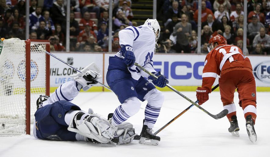 Detroit Red Wings center Gustav Nyquist (14) of Sweden shoots the puck past Toronto Maple Leafs goalie James Reimer (34) during the second period of an NHL hockey game in Detroit, Wednesday, Dec. 10, 2014. (AP Photo/Carlos Osorio)