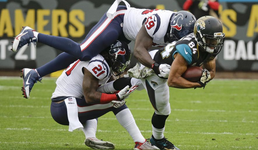 Jacksonville Jaguars wide receiver Cecil Shorts (84) is brought down by Houston Texans free safety Kendrick Lewis (21) and outside linebacker Whitney Mercilus (59) after a 7-yard reception during the first half of an NFL football game in Jacksonville, Fla., Sunday, Dec. 7, 2014. (AP Photo/John Raoux)