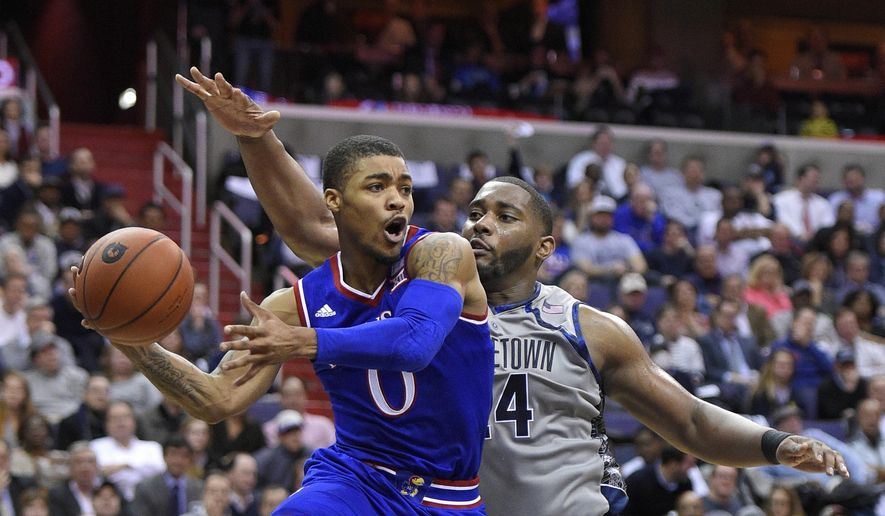 Kansas guard Frank Mason III (0) passes the ball against Georgetown center Joshua Smith (24) during the first half of an NCAA college basketball game, Wednesday, Dec. 10, 2014, in Washington. (AP Photo/Nick Wass)