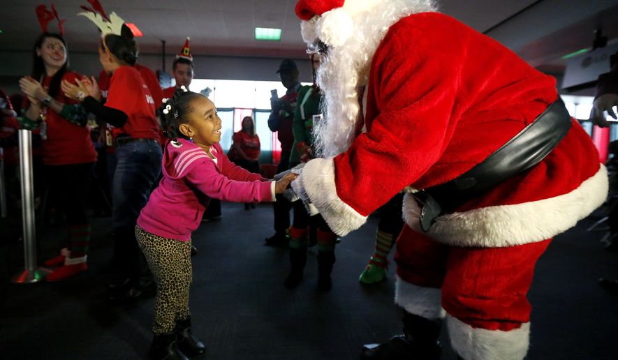 Neorah Reliford, 4, left, of Newark, N.J., is greeted by Santa Claus upon arriving at Newark Liberty International Airport during a fictional flight to the North Pole, Wednesday, Dec. 10, 2014, in Newark, N.J. (AP Photo/Julio Cortez)