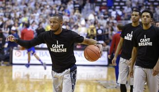 """Georgetown guard Jabril Trawick, left,  wears an """"I Can't Breathe"""" t-shirt during warm ups before NCAA college basketball game on Dec. 10, 2014, in Washington. (Associated Press) ** FILE **"""