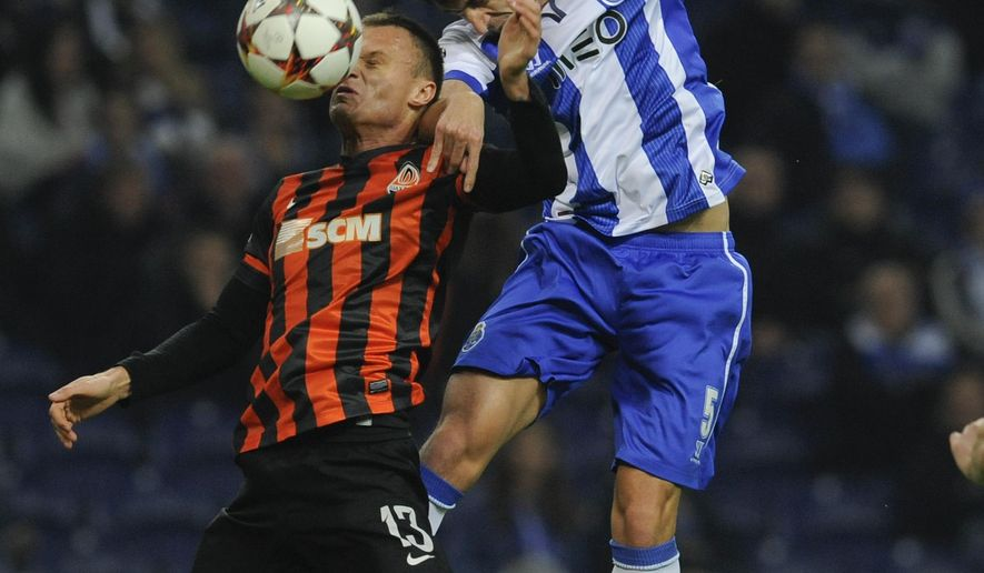 FC Porto Ivan Marcano from Spain, right, challenges for the ball against Vyacheslav Shevchuk of Shakhtar Donetsk during the Champions League Group H soccer match between FC Porto and Shakhtar Donetsk at Dragao Stadium in Porto, Portugal, Wednesday Dec. 10, 2014. (AP Photo/Paulo Duarte)