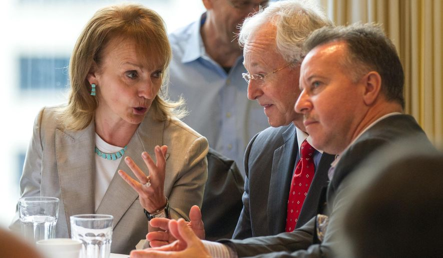 House Speaker Beth Harwell of Nashville confers with fellow Republican Reps. Ron Travis of Dayton, center, and Mike Sparks of Smyrna, during a House GOP caucus meeting in Nashville, Tenn. on Wednesday, Dec. 10, 2014. The caucus later nominated Harwell to another term as speaker of the House. (AP Photo/Erik Schelzig)