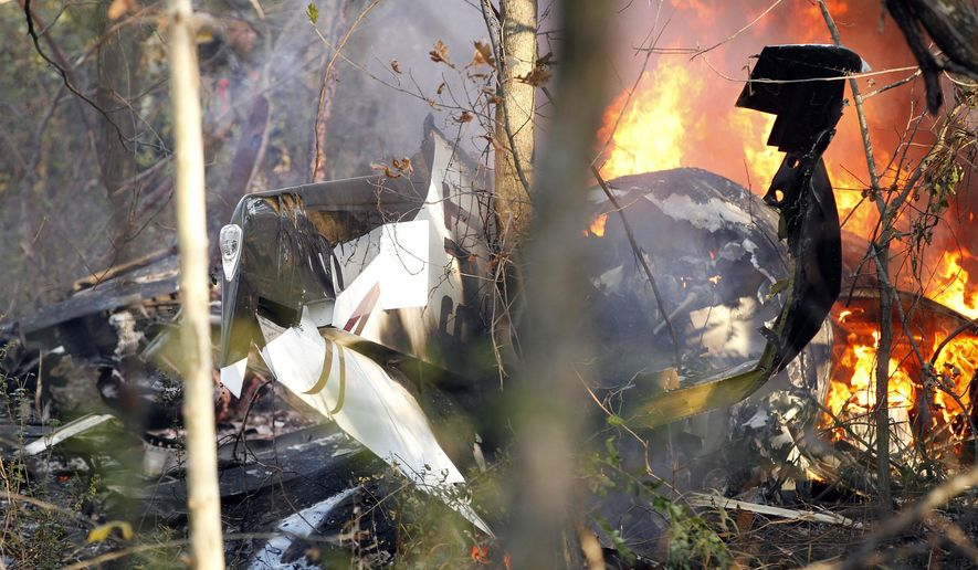 FILE - In this Nov. 10, 2013, file photo, a small plane piloted by Dr. Perry Inhofe, the son of Oklahoma Sen. Jim Inhofe, burns after crashing near a residential area in Owasso, Okla. The family of Sen. Inhofe is seeking damages from the aircraft's manufacturers in a negligence lawsuit. The Tulsa World reports the lawsuit was filed Tuesday in Tulsa County District Court. It says the 2013 crash that killed 51-year-old Perry Dyson Inhofe II was due to manufacturers not providing proper maintenance on the plane's engine and parts. (AP Photo/Tulsa World, Mike Simons, File)