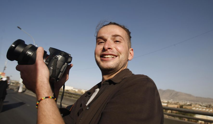 FILE - In this  Feb. 11, 2013 file photo, Luke Somers, 33, an American photojournalist who was kidnapped over a year ago by al-Qaida, poses for a picture during a parade marking the second anniversary of the revolution in Sanaa, Yemen. The body of an American photojournalist killed during a high risk raid to free him and a South African teacher from al-Qaida militants in Yemen is back on U.S. soil. The remains of Luke Somers arrived at Dover Air Force Base Wednesday aboard a U.S. Air Force C-17 aircraft. There was no public announcement. The Somers family was there to receive the remains, but no media coverage was allowed, according to a U.S. defense official who spoke on condition of anonymity because the arrival was not publicly announced.  (AP Photo/Hani Mohammed, File)