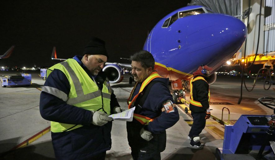 In this Nov 13, 2014 photo, Southwest Airlines ramp supervisor Steve Belch, left, confers with ground crewman Dillard Blue after a mechanical glitch developed on the early morning originator flight waiting for departure from the gate behind them, at Love Field in Dallas. Throughout the airline industry, the first flight of the day sets the tone for keeping the system's flights running on-time. (AP Photo/LM Otero)